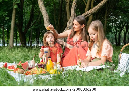 Picnic in summer park. Single mom with little daughters is engaged in drawing on paper and hair care. Combing her youngest daughter.