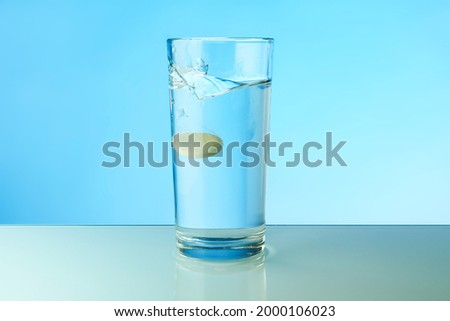 dissolving tablet dissolves in water on colored background. a glass of water and an effervescent vitamin pill. the medicine tablet dissolves in a glass of water