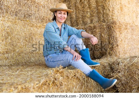 Positive relaxed asian female farmer resting on hayloft after work at farm, sitting on straw stack and smiling. High quality photo