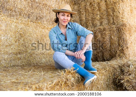Positive relaxed asian female farmer resting on hayloft after work at farm, sitting on straw stack and smiling