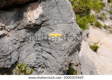 Hiking Trail path Marker on a stone with yellow signs drawn paint sign