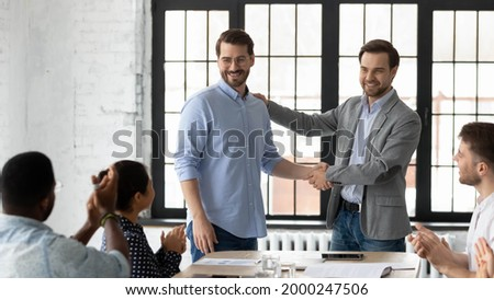 Proud boss encouraging and thanking happy employee for good job, shaking hand. Excited worker getting promotion, recognition, respect and applause of colleagues. Leader introducing new team member Royalty-Free Stock Photo #2000247506