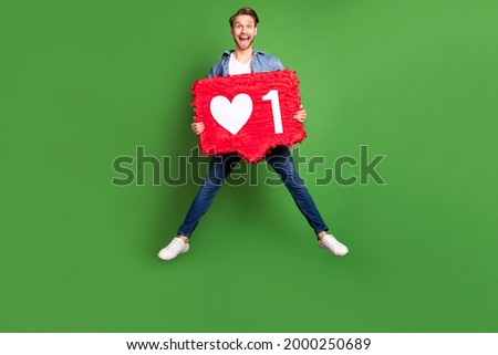 Full length body size photo of amazed guy jumping high keeping social media like isolated bright green color background
