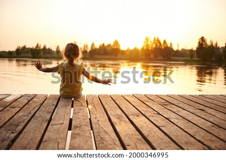 Silhouette of a child sitting on the wooden pier and enjoying heat summer evening at the lake at sunset. Heat summer, summer evenings in nature, spending time in the fresh air Royalty-Free Stock Photo #2000346995