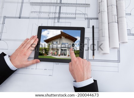 Cropped image of male architect using digital tablet on blueprint in office #200044673