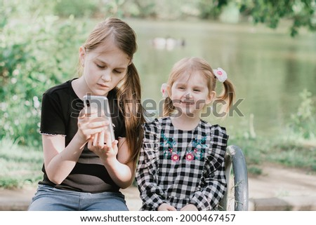 Two sisters sitting on bench in spring summer park near the pond and watching cartoons on smartphone. Wireless technologies concept. Children addiction from gadgets.