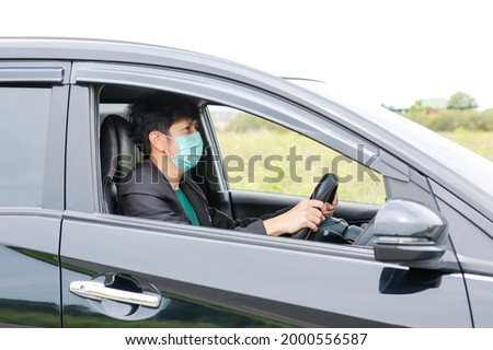 A man wearing a work suit drives a sedan to work in the city. wearing a medical mask to prevent infection during the coronavirus epidemic The driver of the sedan wears a mask for Covid-19. Royalty-Free Stock Photo #2000556587