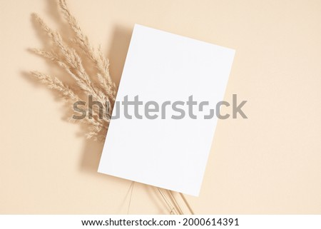 White paper empty blank, dried grass decoration on beige background. Invitation card mockup on beige table. Flat lay, top view, copy space, mockup Royalty-Free Stock Photo #2000614391