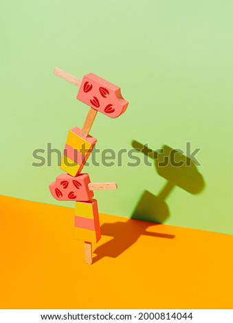 Cartoon ice creams on popsicles standing stacked one over the other on two tone vibrant orange and green background with shadow on the wall. Abstract and surreal summer dessert. Creative food concept.