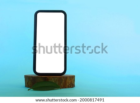 A smartphone with an empty white screen and a green ficus leaf on a wooden stand. Blue background. Space for text. High quality photo