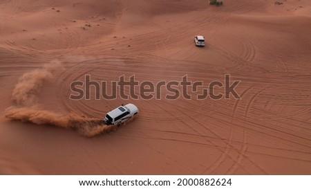 AERIAL. Column of white cars travelling in sand desert. Royalty-Free Stock Photo #2000882624