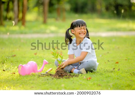 Cute little girl asia planting young tree on black soil in the park.Which increases the development and enhances learning skills as save world new life,environmental conservation concept.