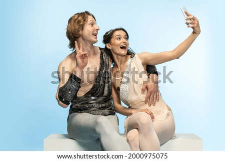 Selfie on mobile phone. Young couple of ballet dancers in ancient Rome costums at blue studio as modern man, woman. Historical character, creative, classical art, humor and comparison of eras concept. Royalty-Free Stock Photo #2000975075