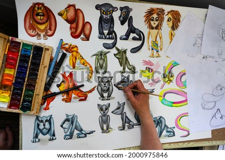 The animator draws with a pencil and draws characters from cartoons, comics or puppet shows. Getting ready to make a doll. The designer creates sketches. Comics, cartoons, puppet theater