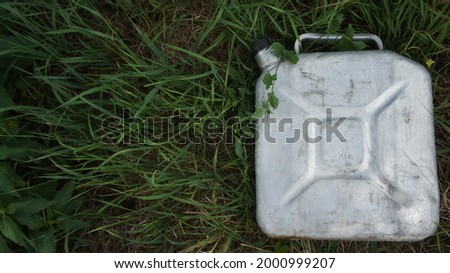 Aluminum can with gasoline in the grass. Biodiesel. Environmental protection. Ecology  Royalty-Free Stock Photo #2000999207