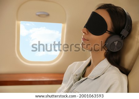 Young woman with sleep mask resting while listening to music in airplane during flight Royalty-Free Stock Photo #2001063593