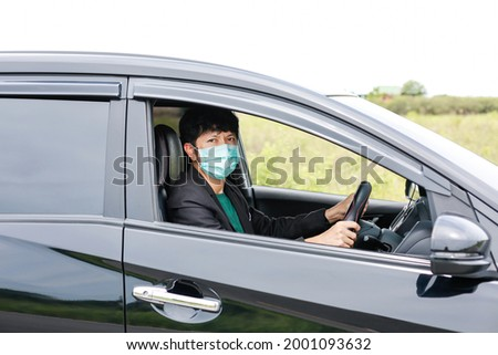 A man wearing a work suit drives a sedan to work in the city. wearing a medical mask to prevent infection during the coronavirus epidemic The driver of the sedan wears a mask for Covid-19. Royalty-Free Stock Photo #2001093632