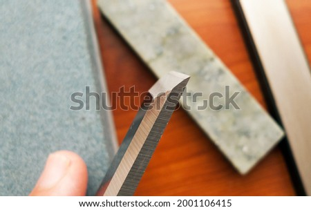 cutting edge of a chisel with sharpening stones in unfocused background image