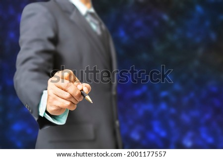 Portrait business man wearing a black suit stand and hold pen for writing or drawing on dark blue tone background (select focus at hand)