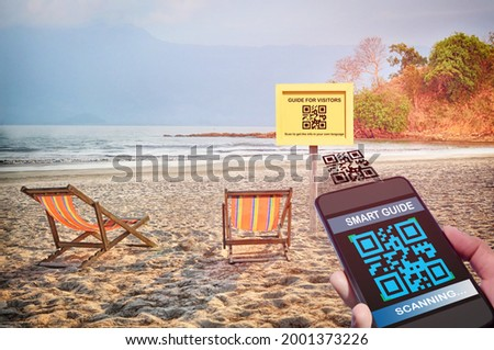 Hand holding smartphone with scanning QR code smart guide screen with guide for visitors sign on tropical beach background. Smart technology concept and qr code quick and easy idea