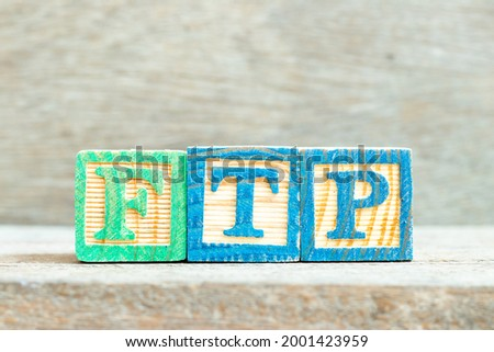 Color alphabet letter block in word FTP (Abbreviation of File Transfer Protocol) on wood background
