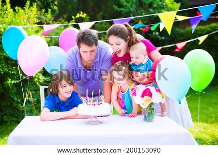 Happy big family with three kids - school age boy, toddler girl and a little baby enjoying birthday party with a cake blowing candles in a summer garden decorated with balloons and banners #200153090