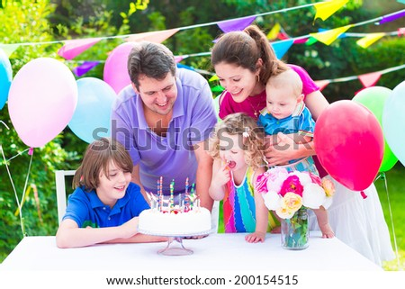 Happy big family with three kids - school age boy, toddler girl and a little baby enjoying birthday party with a cake blowing candles in a summer garden decorated with balloons and banners #200154515