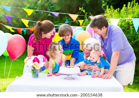 Happy big family with three kids - school age boy, toddler girl and a little baby enjoying birthday party with a cake blowing candles in a summer garden decorated with balloons and banners #200154638