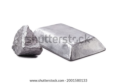 Isolated zinc ingot or bar next to raw zinc nugget on isolated white background, metal used in alloy and steel production. Royalty-Free Stock Photo #2001580133