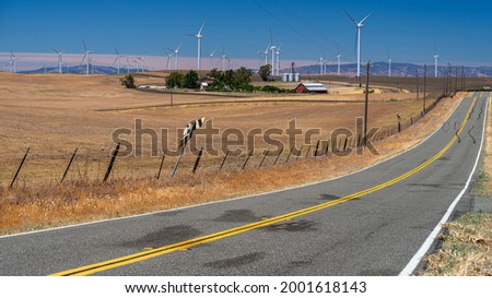 The Shiloh wind power plant is a wind farm located in the Montezuma Hills of Solano County, California. A farmhouse and silo blend amongst the wind turbines in a scenic environment. Royalty-Free Stock Photo #2001618143
