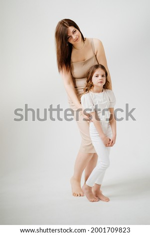Mom and daughter pose in a white photo studio. Happy family. single mother with child. center for psychological assistance to families. clothing store.