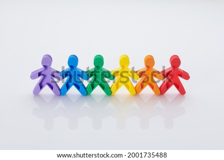 Rainbow, colourfull people concept. High resolution photo for graphic design. Diffrent race, diffrent skin colour concept, plastic people statuettes holdings hands.