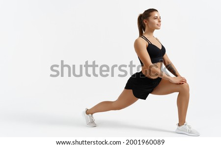 Beautiful female athlete stretching before workout indoors. Sport woman stretch legs, doing gym exercises alone isolated white background, silhouette of girl warming up Royalty-Free Stock Photo #2001960089