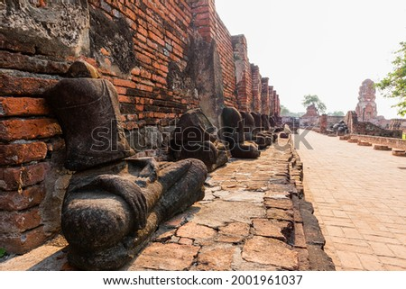 Landscape view of Wat Maha That in Ayutthaya historical park of Thailand and also it is the world heritage by Unesco. In this picture can see many Buddha Images were placed at the temple wall.