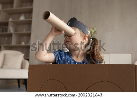 Cute adorable little girl in black pirate hat looking in spyglass, sitting in toy cardboard ship, preschool child kid wearing homemade costume holding cardboard tube as telescope, playing funny game Royalty-Free Stock Photo #2002021643