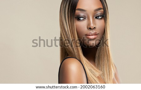 Beautiful African American woman with dyed and straight hair. The beauty of an afro black girl with a bob smooth hairstyle and toning. Keratin straightening. Treatment, care and spa procedures. Royalty-Free Stock Photo #2002063160