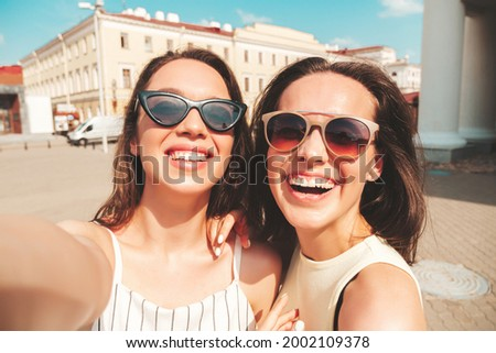 Two young beautiful smiling hipster female in trendy summer clothes.Sexy carefree women posing on the street background in hat. Positive pure models having fun at sunset, taking Pov photos in the city