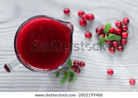 Homemade fresh wild lingonberry sauce in a glass gravy boat, top view, flat lay