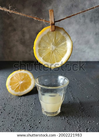 Still life photography with a glass of lemon juice, lemon slices hanging on a rope and sliced lemon on the table with a dark grey background.