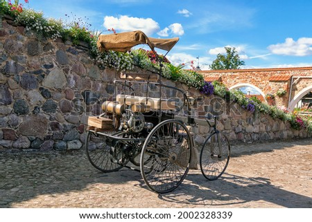 Pakruojis, Lithuania - 2020 August 28 Pakruojis Manor Park. An ancient four-wheeled motor carriage to the wall Royalty-Free Stock Photo #2002328339