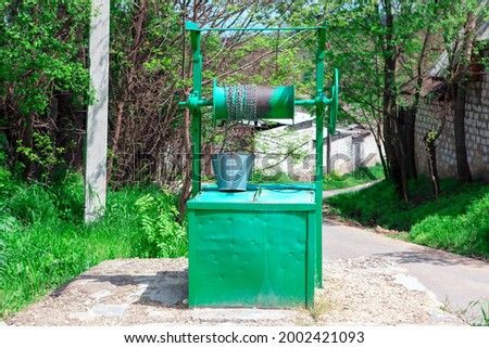 Well bucket and chain . Water source in the village