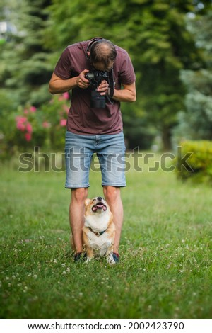 Young man making a photo of welsh corgi pembroke dogs with a professional dslr camera