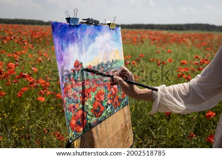 Mature woman artist paints a picture on a poppy field. Close-up - hand with a brush