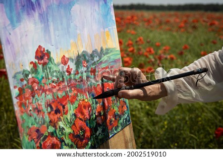 Close-up - womens hand with a brush paints a picture on a poppy field