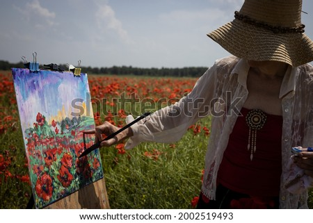 Mature woman artist paints a picture on a poppy field,  hand with a brush