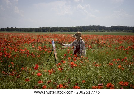Mature woman artist paints a picture on a poppy field in sunny day