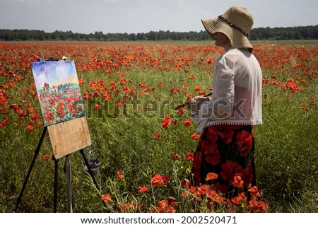 Mature woman artist paints a picture on a poppy field, side view