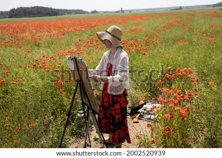 Mature woman artist paints a picture on a poppy field. Plein air in a beautiful place