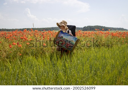 A mature woman artist with a painted picture returns from the open air in a poppy field.