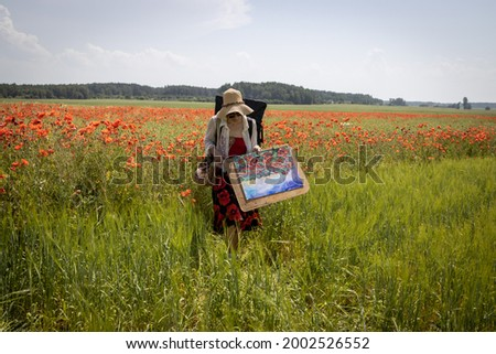 A mature woman artist with a painted picture returns from the open air. Poppy field.